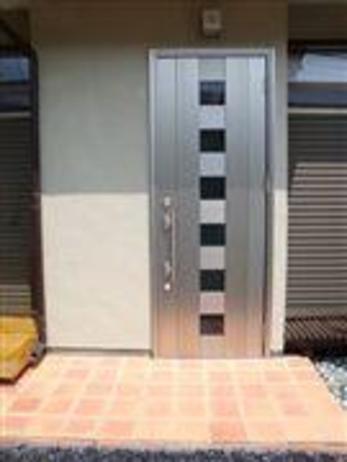 玄関扉は築20年以上の建物に見られる引き違い戸だったものをシャープでモダンな片開き扉にしました。そして玄関タイルは気分が明るくなるような色のタイルを使用して施工しました。